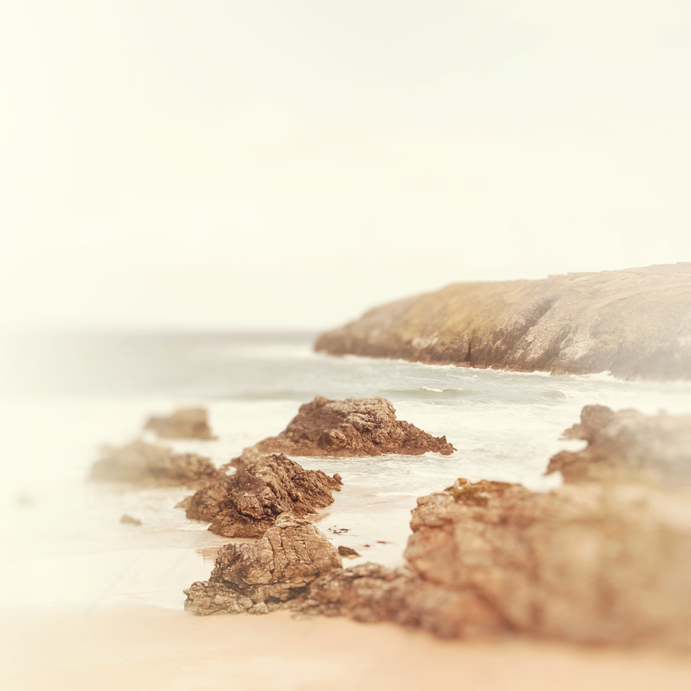 Photograph of a rocky beach, and water, along the coast of The Highlands in Northern Scotland.
