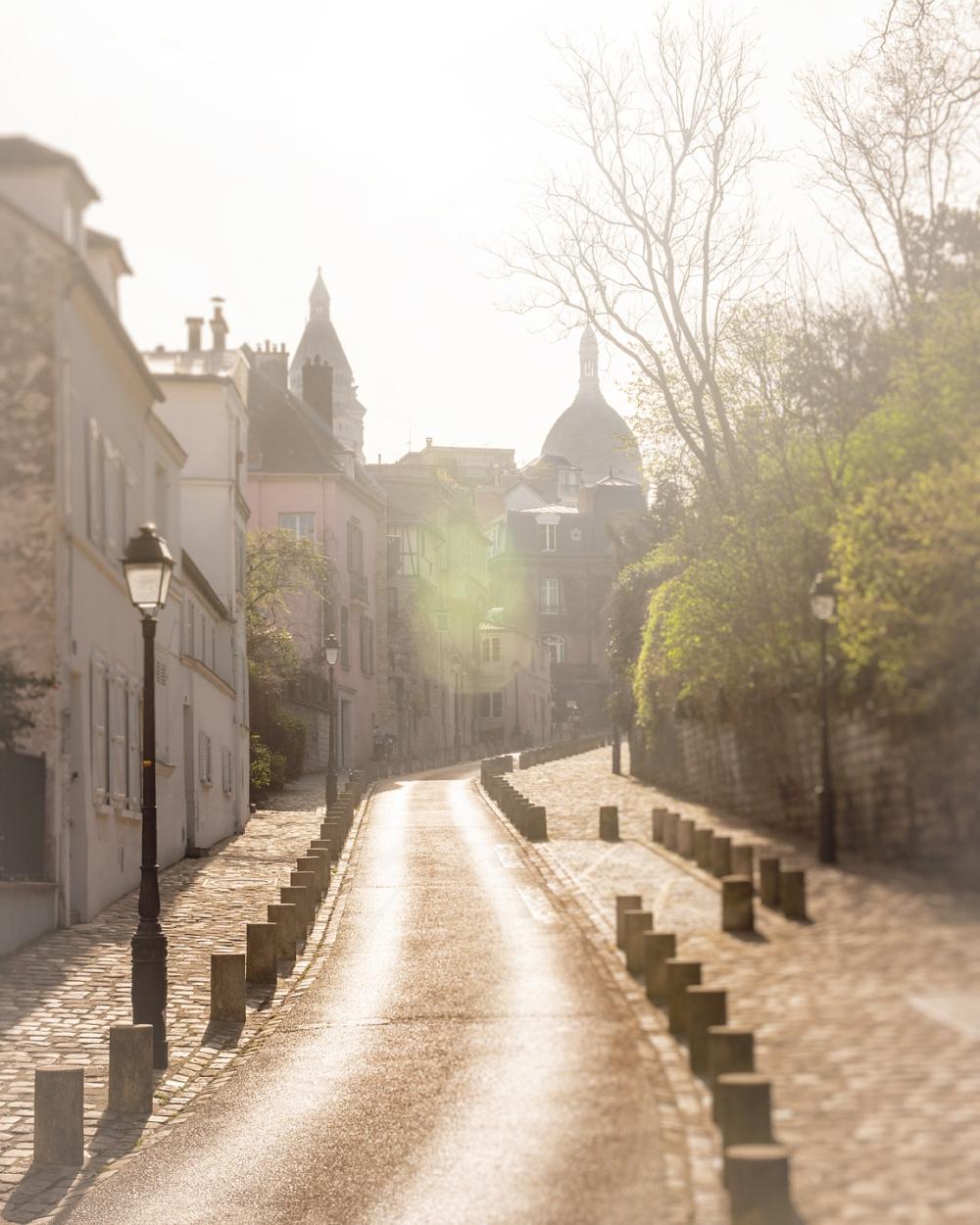 A morning walk along a winding road leading up to Sacré-Cœur which is in silhouette in the background by Chicago artist Tracey Capone