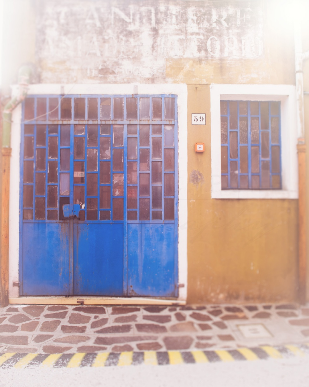 Bright blue door against a mustard yellow wall on the island of Burano, Italy. Travel and architecture photography by Tracey Capone.